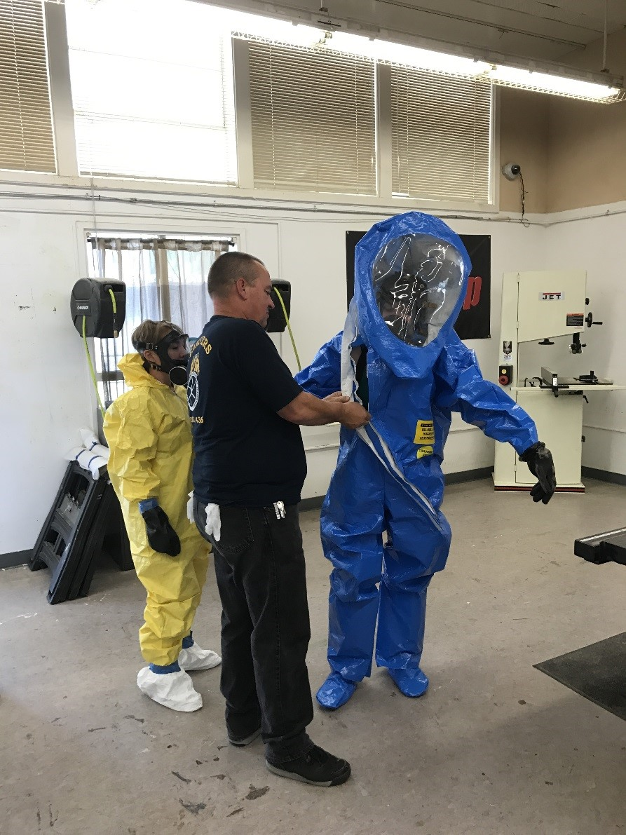 Esther gearing up in the blue Level A PPE suit
